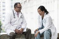 Hispanic man and Asian woman doctors conferring over a case in a hospital. - MINF08955