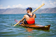 A man paddles a wooden kayak in Bear Lake, Utah. - AURF01174
