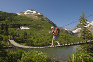 A young girl hikes over a suspension bridge in Glacier National Park, Montana. - AURF01242