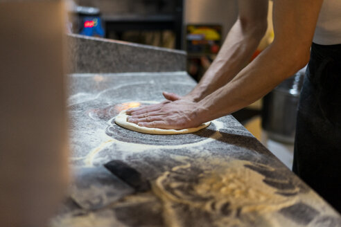 Close-up of pizza baker preparing pizza dough in kitchen - AFVF01450