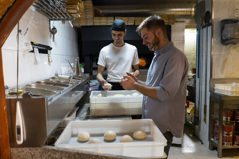 Two men with raw dough in boxes in kitchen of a pizzeria - AFVF01456