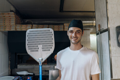 Portrait of smiling pizza baker holding pizza peel in kitchen - AFVF01471