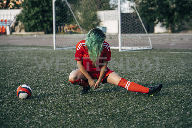 Young woman stretching on football ground next to the ball - VPIF00507