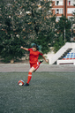 Young woman playing football on football ground shooting the ball - VPIF00510