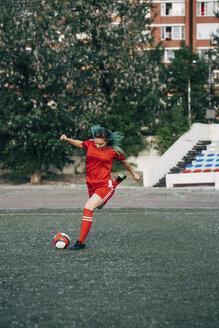 Young woman playing football on football ground shooting the ball - VPIF00510