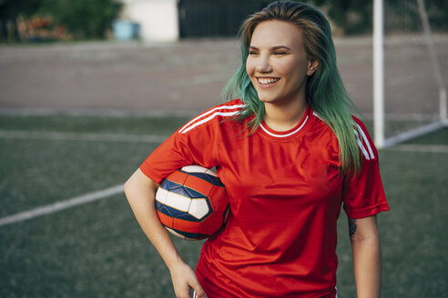 Smiling young woman standing on football ground holding the ball - VPIF00513