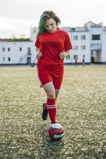 Young woman playing football on football ground running with the ball - VPIF00516
