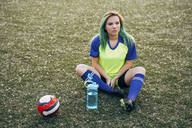 Young woman sitting on football ground with water bottle and ball - VPIF00519