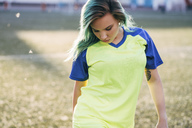 Portrait of young woman in jersey on football ground looking down - VPIF00522