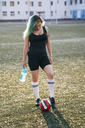 Young woman standing on football ground with ball and bottle of water - VPIF00525