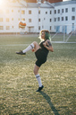 Young woman playing football on football ground balancing the ball - VPIF00528