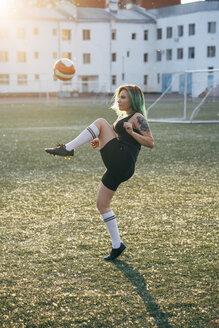 Young woman playing football on football ground balancing the ball - VPIF00528