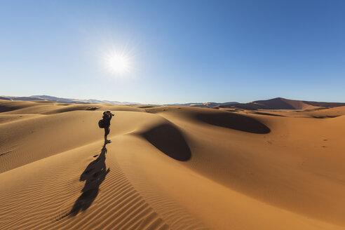 Africa, Namibia, Namib desert, Naukluft National Park, female photograper on sand dune against the sun - FOF10096