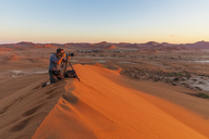Africa, Namibia, Namib desert, Naukluft National Park, photograper on sand dune at sunrise - FOF10102