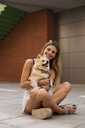 Smiling young woman sitting, holding her dog - ACPF00245