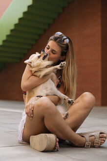 Smiling young woman sitting and kissing her dog - ACPF00254