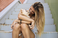 Smiling young woman sitting on stairs, holding her dog - ACPF00257