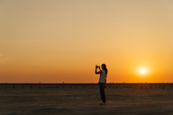 Germany, Schleswig-Holstein, Sankt Peter-Ording, woman taking a picture on the beach at sunset - UMF00833