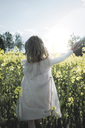 Back view of little girl walking on mother's hand in rape field - PSIF00014