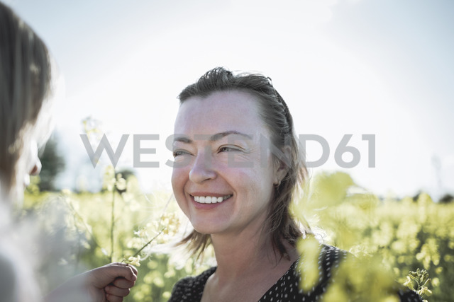 Portrait of smiling mother in rape field - PSIF00017