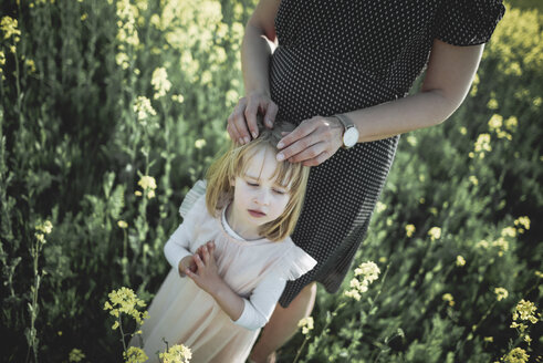 Portrait of little girl standing with her mother in rape field - PSIF00020