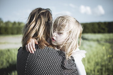 Portrait of little girl on her mother's arms in rape field - PSIF00026