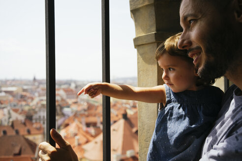Czechia, Prague, father and little daughter looking together at view from the old town hall - GEMF02297