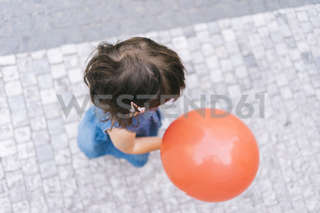 Baby girl with red balloon walking on pavement, top view - GEMF02306