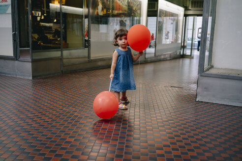 Portrait of baby girl with two red balloons standing in a passage - GEMF02309