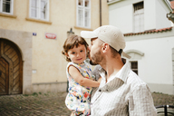 Czechia, Prague, portrait of smiling baby girl on her father's arms - GEMF02318