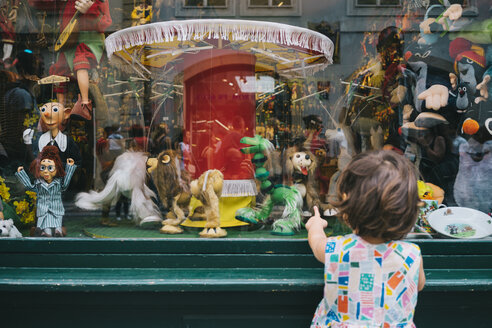Czechia, Prague, back view of little girl standing in front of toy shop looking at puppets - GEM02324