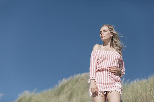 Young woman standing on beach dune under blue sky - JESF00117