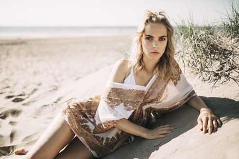Portrait of a young woman lying in beach dune - JESF00120