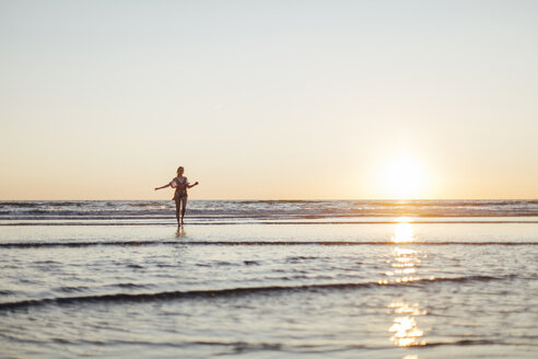 Young woman standing in the sea at sunset - JESF00132