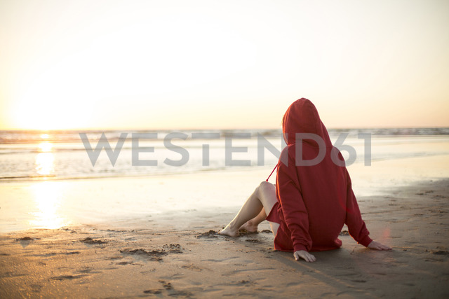 Young woman wearing red hooded jacket sitting on the beach at sunset - JESF00138 - Jean Schwarz/Westend61