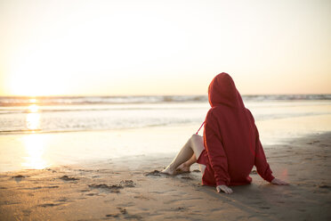 Young woman wearing red hooded jacket sitting on the beach at sunset - JESF00138