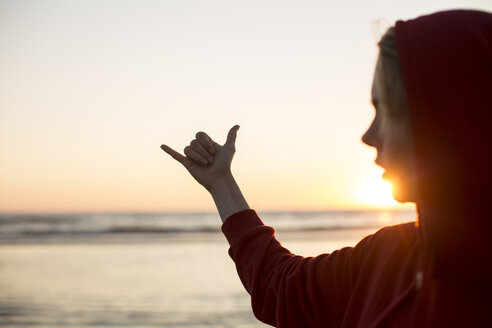 Young woman wearing red hooded jacket on the beach at sunset making hang loose gesture - JESF00141