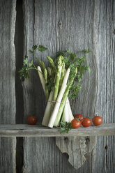 Bundle of green and white asparagus, tomato, parsley and mixed pepper on wood - ASF06203