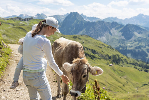 Germany, Bavaria, Oberstdorf, mother and little daughter meeting a cow during a hike in the mountains - DIGF04966