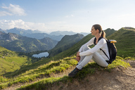 Germany, Bavaria, Oberstdorf, woman on a hike in the mountains having a break - DIGF04978