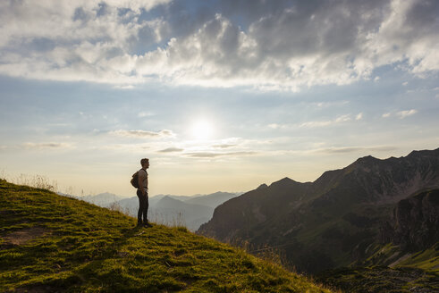 Germany, Bavaria, Oberstdorf, man on a hike in the mountains looking at view at sunset - DIGF04984