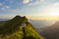 Germany, Bavaria, Oberstdorf, man hiking on a ridge in the mountains at sunset - DIGF04987