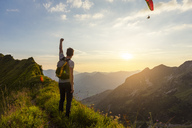 Germany, Bavaria, Oberstdorf, man on a hike in the mountains at sunset with paraglider in background - DIGF04990