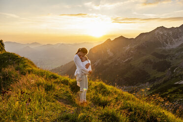 Germany, Bavaria, Oberstdorf, mother holding little daughter on a hike in the mountains at sunset - DIGF04993