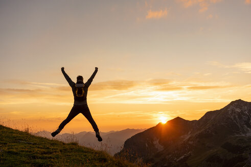 Germany, Bavaria, Oberstdorf, man on a hike in the mountains jumping at sunset - DIGF04996