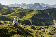 Germany, Bavaria, Oberstdorf, mother and little daughter on a hike in the mountains having a break - DIGF04999