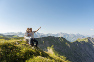 Germany, Bavaria, Oberstdorf, family with little daughter on a hike in the mountains having a break looking at view - DIGF05002