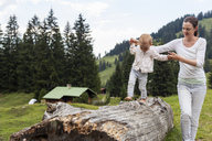 Germany, Bavaria, Oberstdorf, mother helping little daughter balancing on a log - DIGF05005