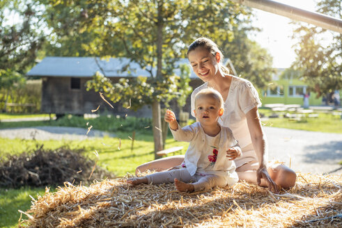Happy mother and little daughter playing with straw on a farm - DIGF05011
