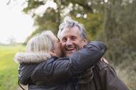 Portrait happy, playful mature couple hugging in park - HOXF03716